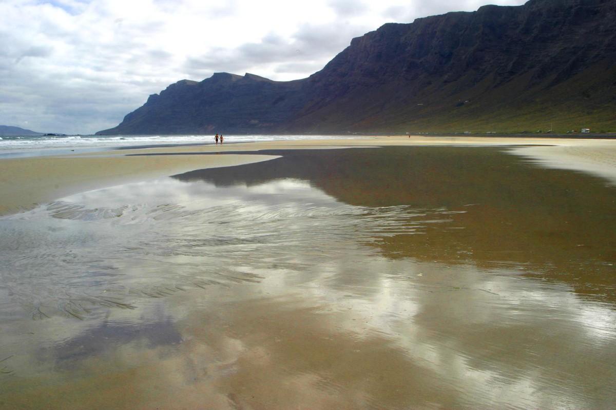 playa de famara marea baja reflejo rilsco en la arena.